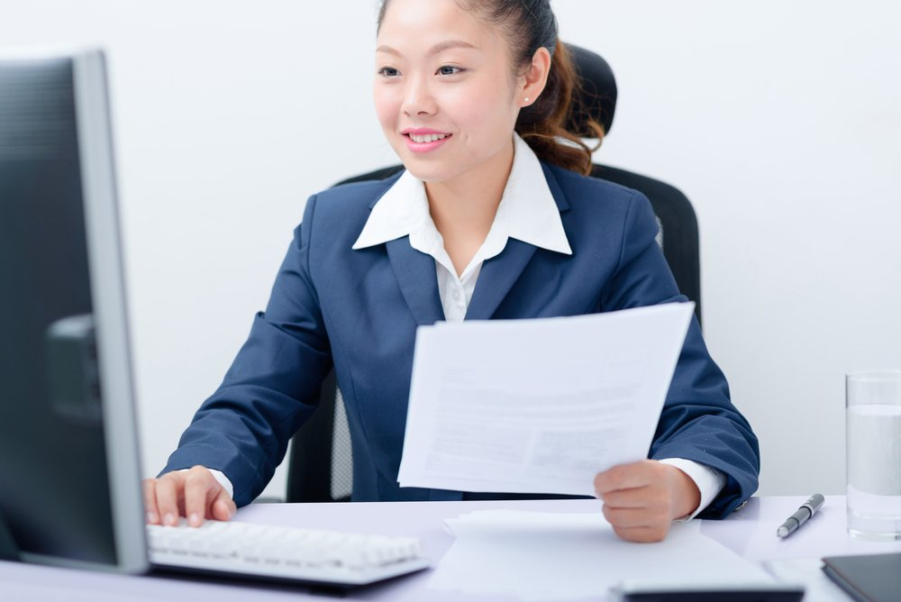 woman holding a couple papers and working at her desktop computer