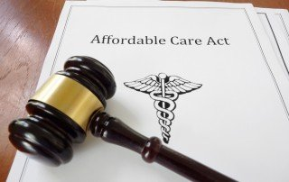 "Gavel lying across a document with ""Affordable Care Act"" written on the title page"