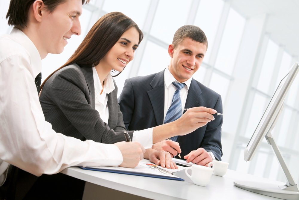 Three business people working in office at computer