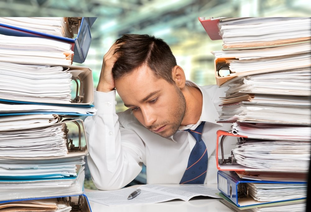 Business man with head down between two huge stacks of paperwork