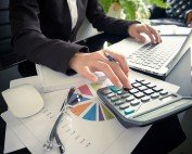 Close up business woman calculating costs with calculator and computer
