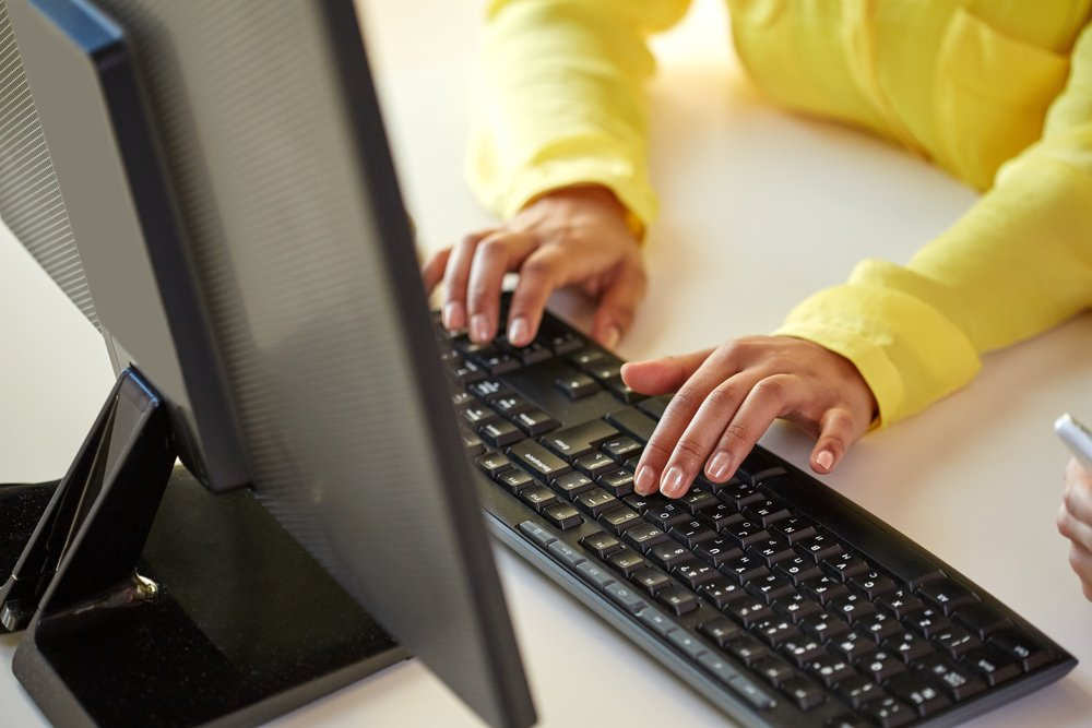 close-up of woman in yellow blouse typing on computer keyboard