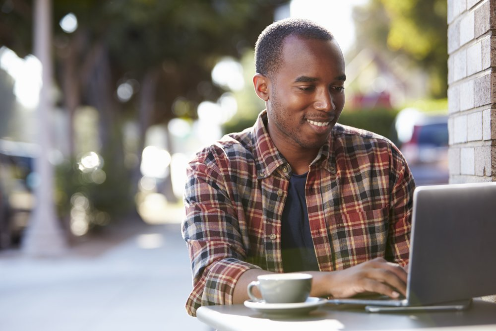 Man sitting at outside table working on computer