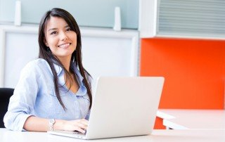 Young woman in blue blouse working on laptop