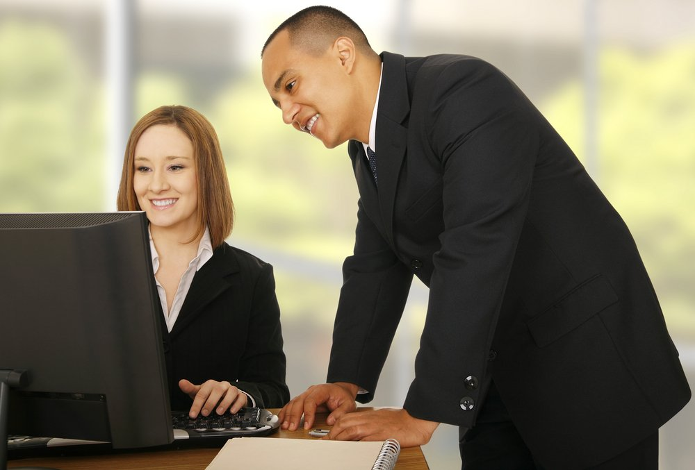 Two business people looking at computer monitor in office setting