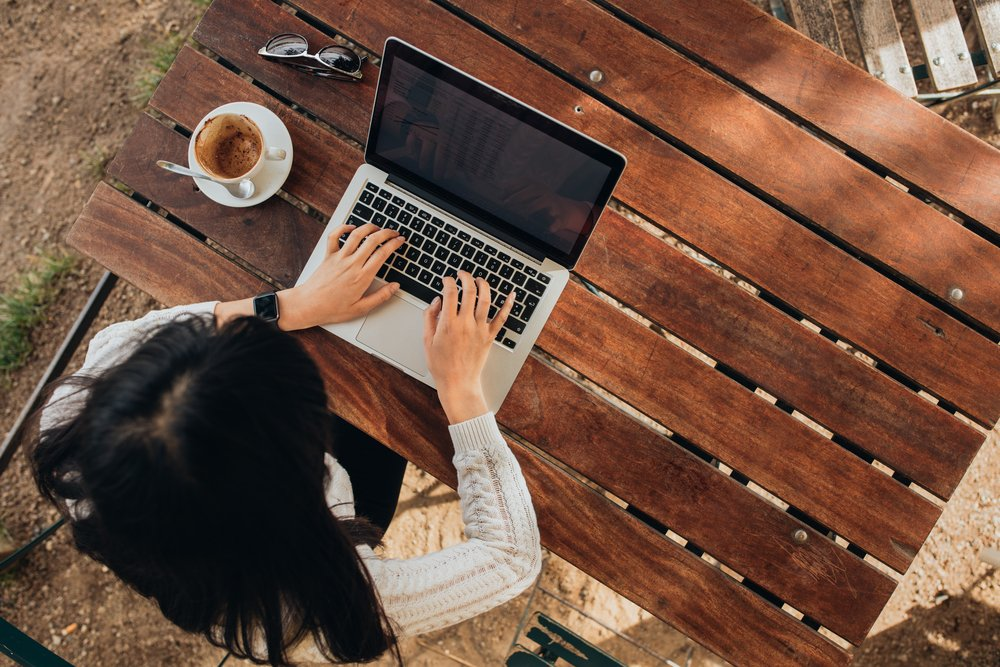 Overhead shot of young woman working on laptop at an outside talbe