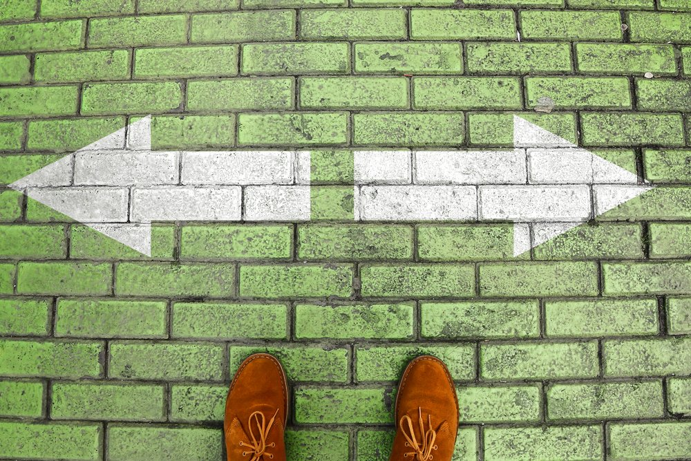 Overhead shot of person wearing suede shoes standing on green brick crossroad with white arrows pointing in opposite directions