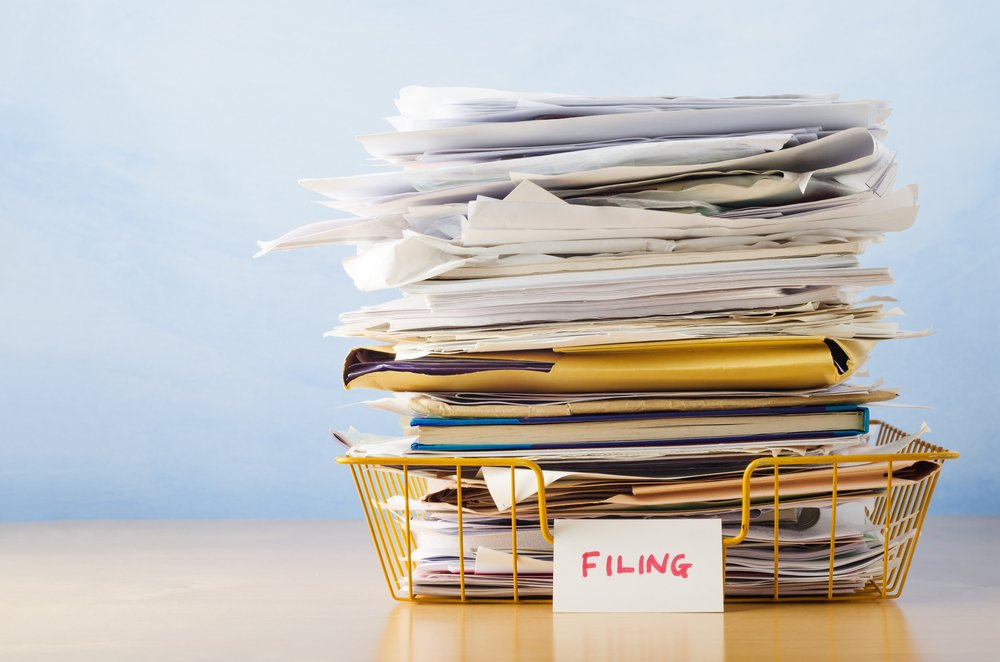 "Stack of papers and folders in a wire basket with card labeled ""file"" leaning against it"
