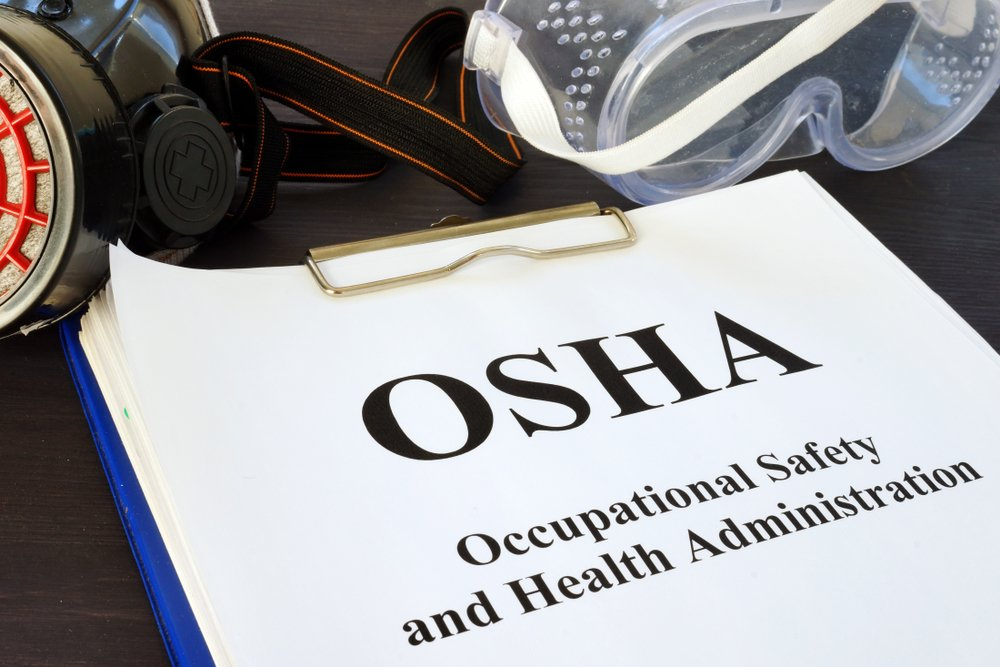 """Clipbard with stack of papers. Top one shows """"OSHA"""""""