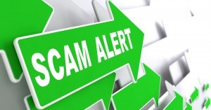 "The words ""SCAM ALERT"" written in white all capital letters on a green arrow that is part of a group of arrows pointing to the right."