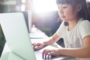 Young Asian girl using laptop at home