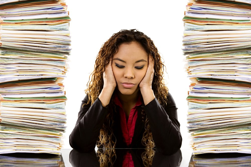 Young woman sitting at desk, head in her hands, between two tall stacks of paper