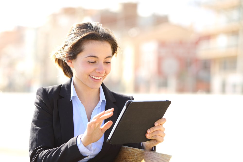 Young woman working outside on mobile tablet