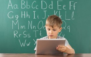 Young boy working on mobile tablet while sitting in front of green chalkboard with alphabet printed on it