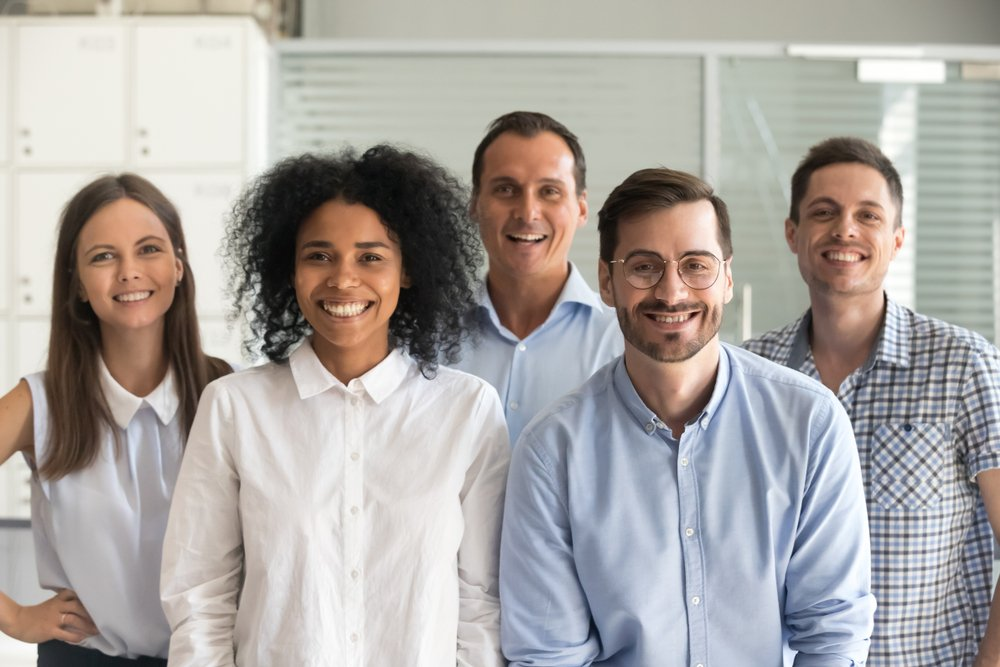 Diverse group of office workers standing together and smiling at camera