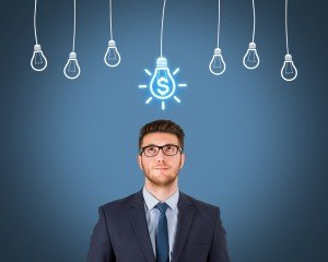Businessman looking up at chalk-drawn row of light bulbs. One has a dollar sign in it.