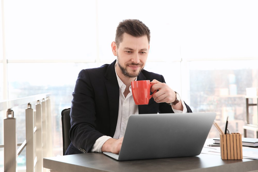 Business man with red mug working on a laptop