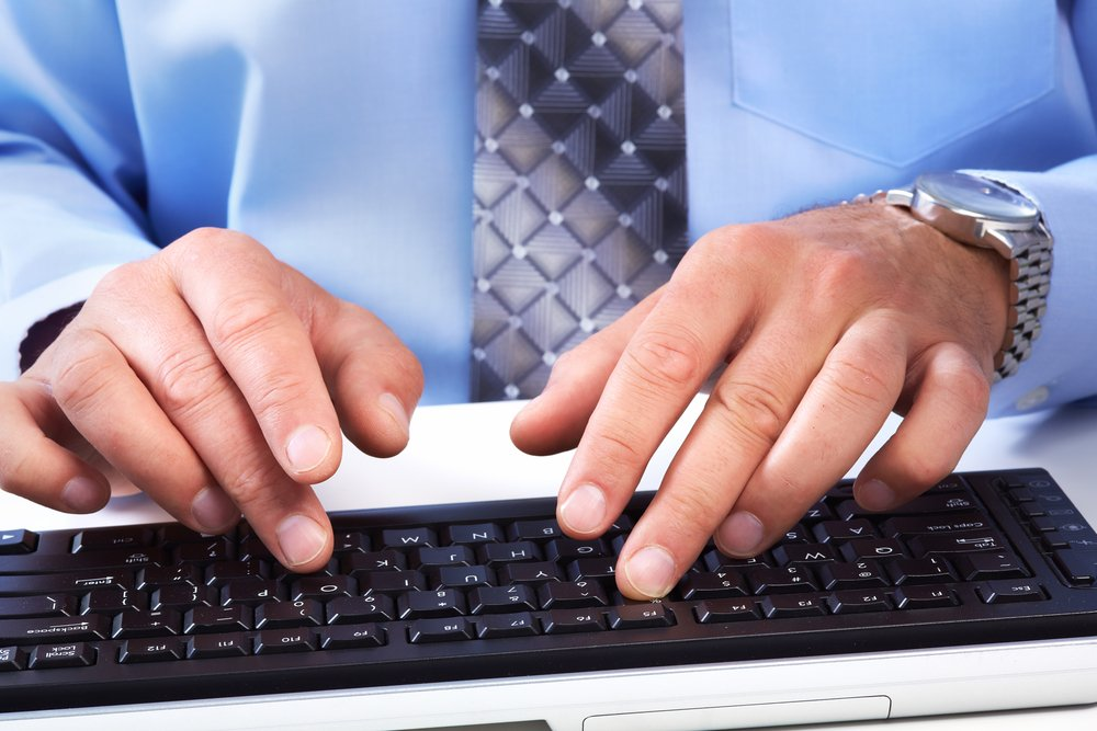 close up of man in blue shirt and tie typing on computer keyboard in office
