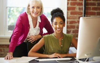 Older business woman mentoring younger business woman sitting at computer