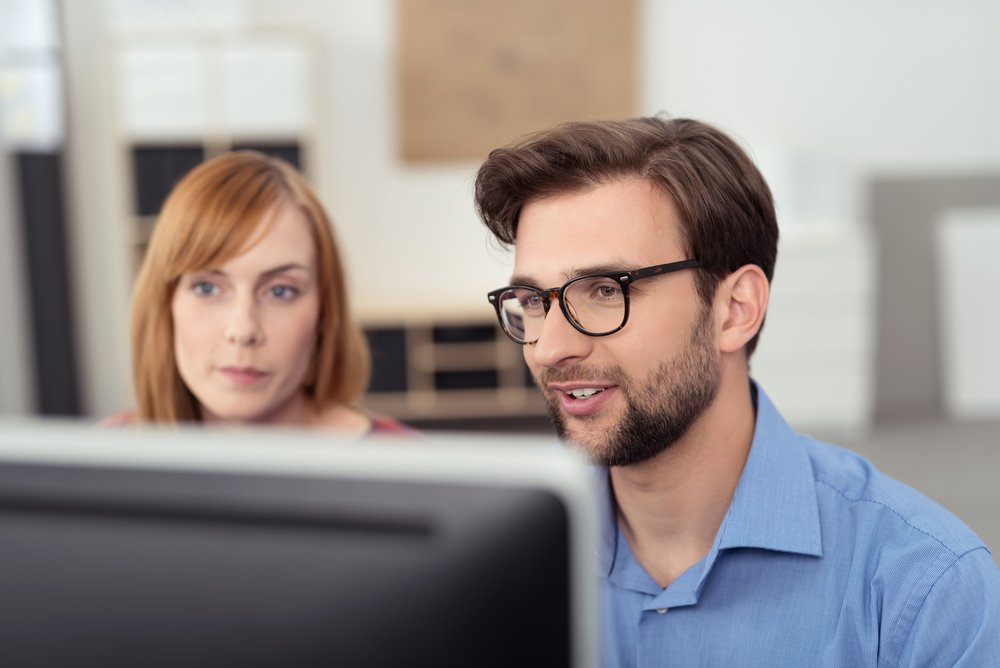 Two young business people looking at computer monitor in office