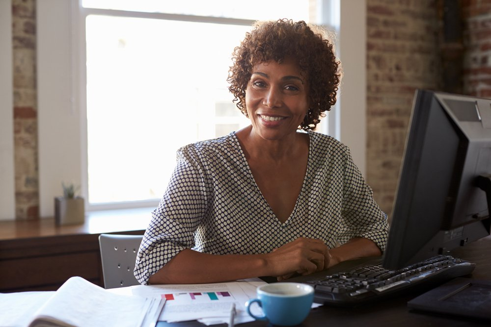 A business woman sitting at her computer in a brick-walled office