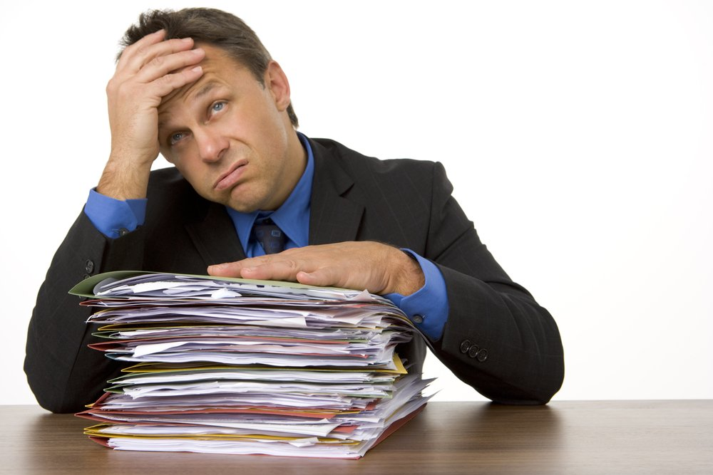 Unhappy businessman sitting at desk, one hand on his forehead, the other resting on a large stack of paperwork.