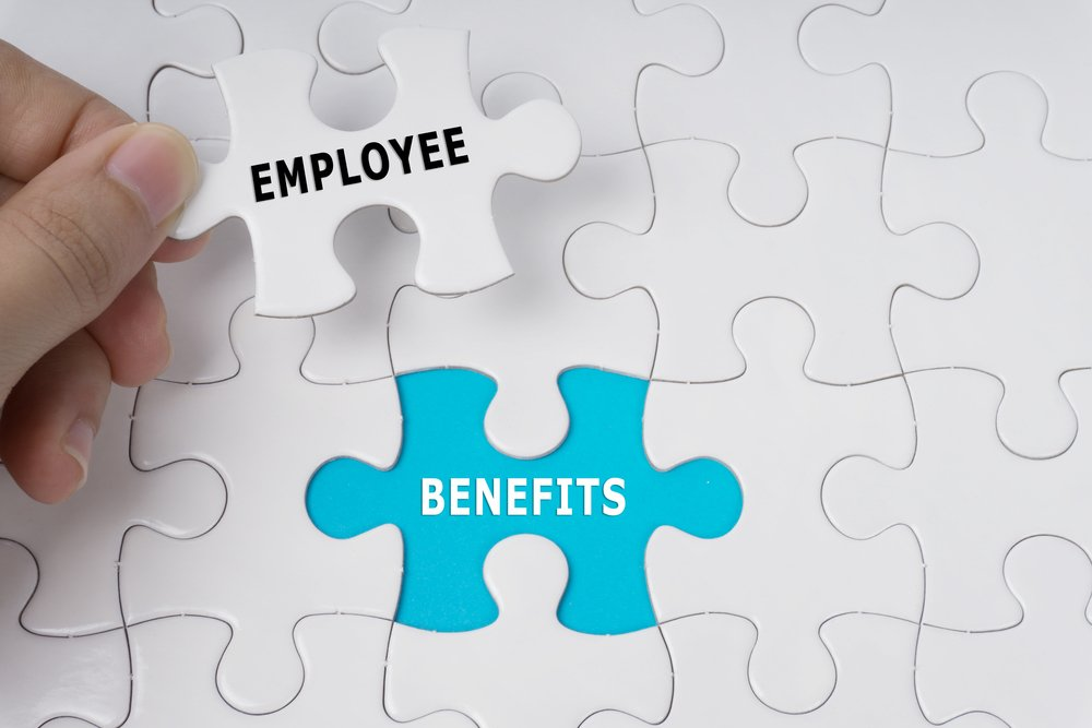 "Hand holding a white puzzle piece with the word ""Employee"" ready to fit it into blue space with word ""Benefits"" showing"