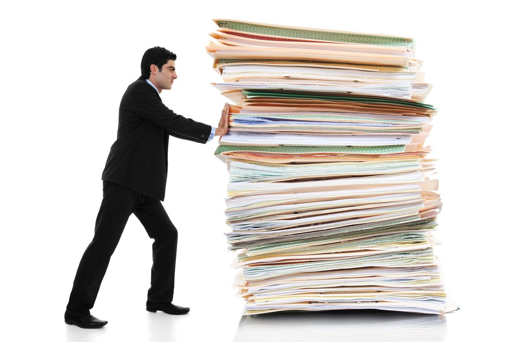 small man pushing a large stack of paper files