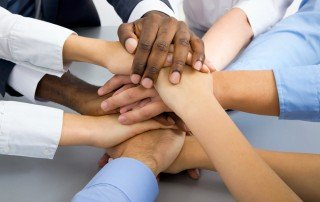 hands of diverse business team members stacked on top of one another signifying teamwork