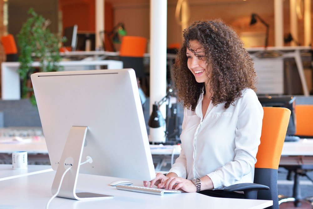 Smiling woman working at her computer in office