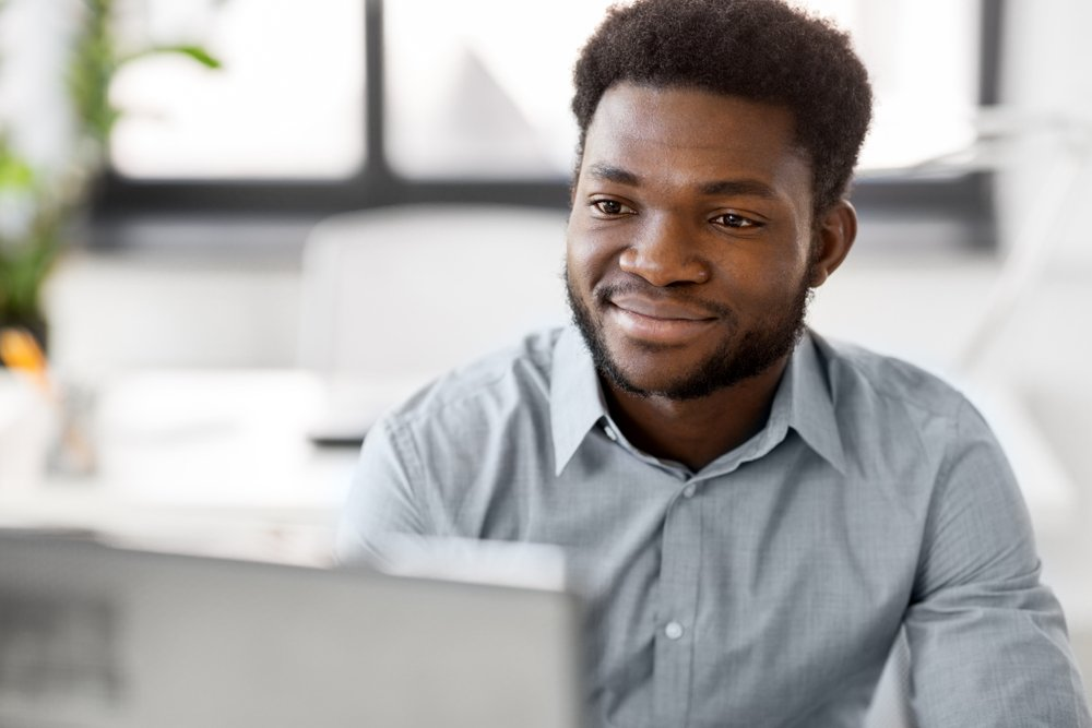 Smiling African American businessman at office computer
