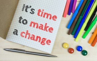 "Words ""It's time to make a change"" on quadrille tablet surrounded by colored pens"