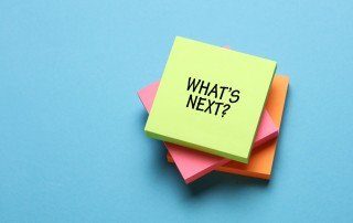 """A stack of colorful Post-it notes with """"What's Next?"""" written on the top sheet"""