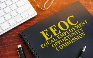 """Dark notebook with """"EEOC Equal Employment Opportunity Commission"""" written on cover, resting on desk with glasses, keyboard, and pen"""